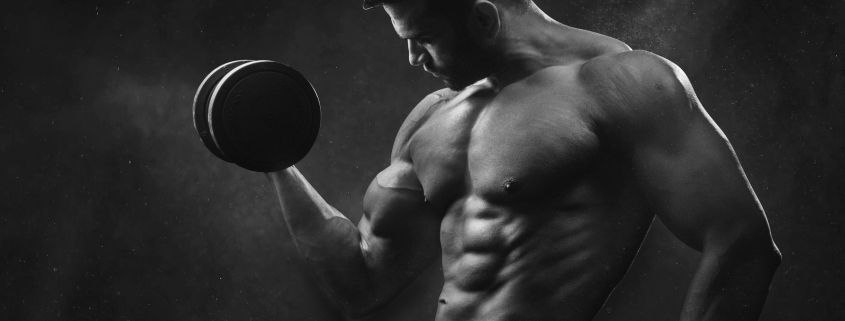 muscular man holding dumbbell